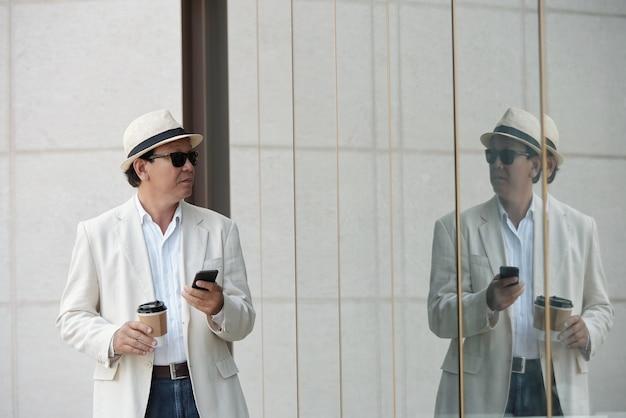 Poważny dojrzały wietnamski biznesmen z filiżanką kawy i gadżetem, patrzący na swoje odbicie w szklistym budynku na zewnątrz