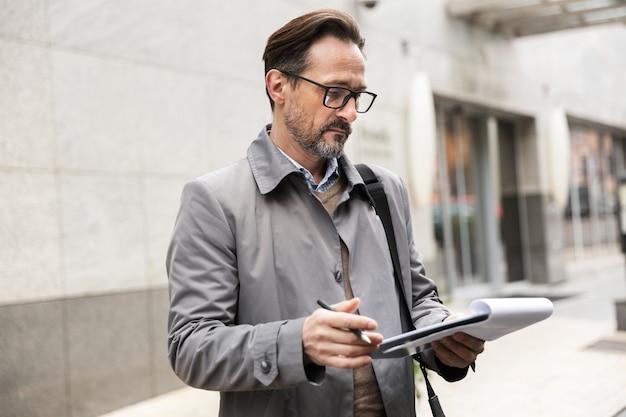 Poważny dorosły biznesmen w okularach, trzymający schowek i czytający, stojąc w pobliżu biurowca