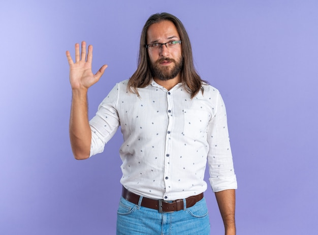 Poważny dorosły przystojny mężczyzna w okularach pokazujących pustą rękę