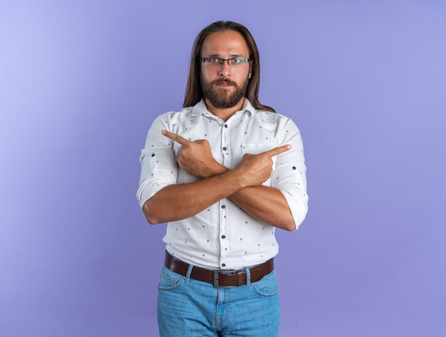 Poważny dorosły przystojny mężczyzna w okularach trzymający ręce skrzyżowane, wskazujące na boki, patrzący na kamerę odizolowaną na fioletowej ścianie z miejscem na kopię