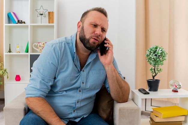 Poważny dorosły słowiański mężczyzna siedzi na fotelu rozmawiając przez telefon w salonie