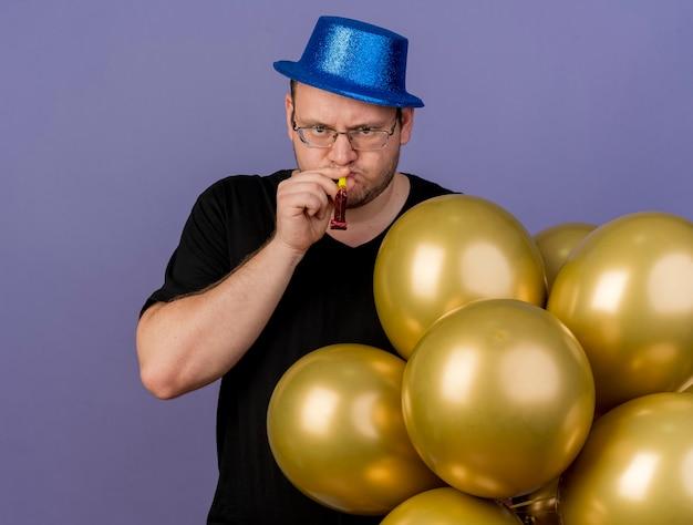 Poważny dorosły słowiański mężczyzna w okularach optycznych w niebieskim kapeluszu imprezowym stoi z balonami z helem dmuchającym w gwizdek!