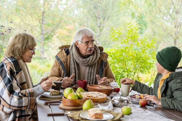 Poważny dziadek w ciepłym ubraniu i wełnianym szaliku z dzianiny rozmawiający z wnukiem przy serwowanym stole podczas kolacji na świeżym powietrzu z babcią