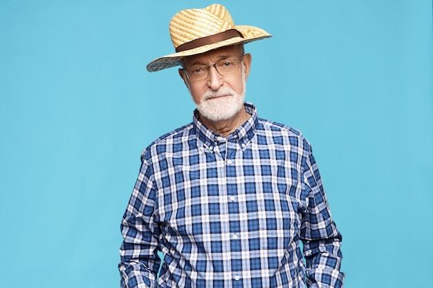 Poważny emeryt starszego mężczyzny z siwą brodą spędza lato na wsi, pozowanie na białym tle, ubrany w niebieską kraciastą koszulę i słomkowy kapelusz. osoby starsze, dojrzały wiek, styl życia i emerytura
