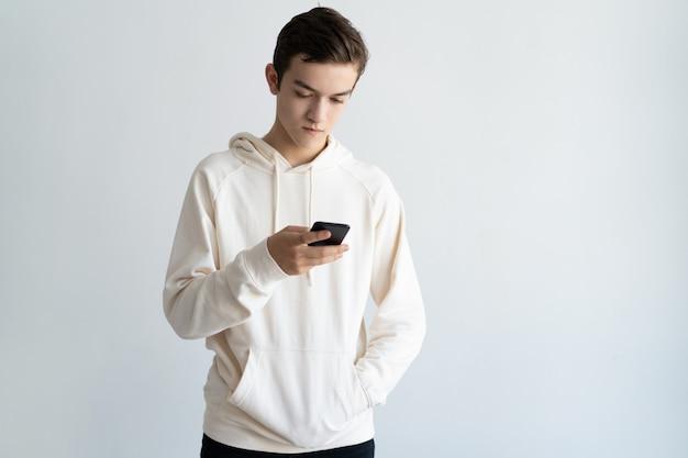Poważny facet koncentruje się na ekranie smartfona