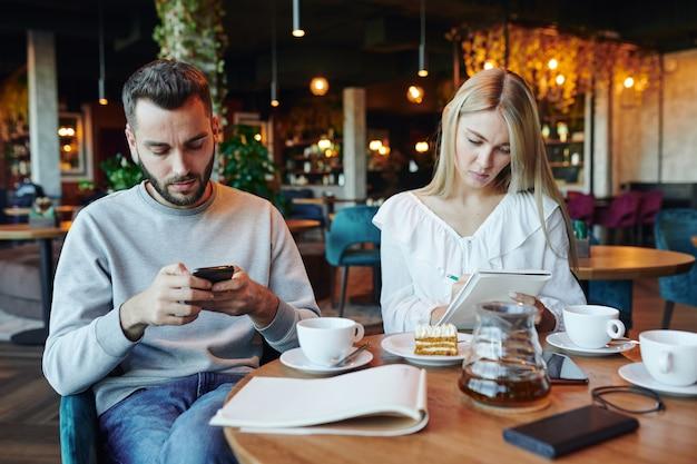 Poważny facet przewijający w smartfonie, podczas gdy jego dziewczyna robi notatki w notatniku przy filiżance herbaty w kawiarni uczelni