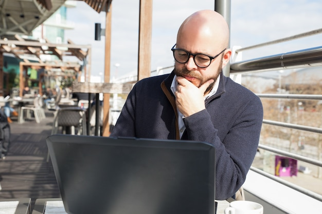 Poważny facet używa laptop w plenerowej kawiarni