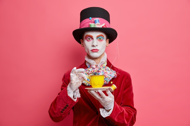 Poważny fikcyjny kapelusznik z kolorowym makijażem pije kawę ma białą twarz ubraną w kostium na halloween i patrzy poważnie na aparat odizolowany na różowej ścianie