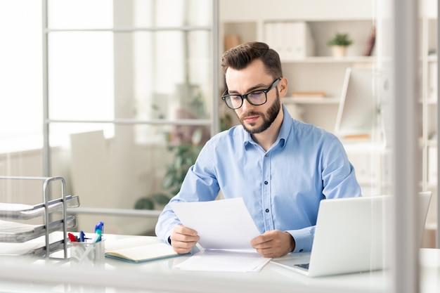 Poważny finansista w sprytnym, swobodnym czytaniu dokumentów finansowych przy biurku podczas przygotowywania dokumentów do transakcji