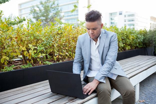 Poważny freelancer pracuje na laptopie outdoors