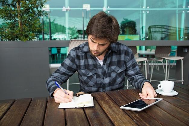 Poważny freelancer pracuje w kawiarni na świeżym powietrzu