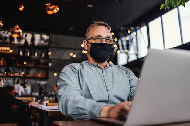 Poważny freelancer w średnim wieku z okularami i maską ochronną na siedzeniu w kawiarni i korzystaniu z laptopa podczas wybuchu koronawirusa.