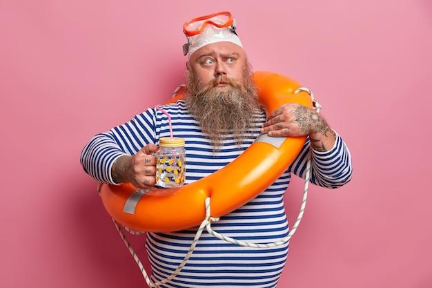 Poważny grubas marszczy brwi, trzyma szklaną butelkę wody, w upalny dzień czuje pragnienie, nosi marynarski sweter w paski, okulary pływackie, pozuje z nadmuchanym kołem ratunkowym do bezpiecznego pływania. urlop bezpieczeństwa