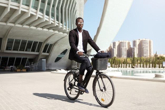 Poważny i pewny siebie młody pracownik biurowy afroamerykanów ubrany w lustrzane okulary przeciwsłoneczne i formalny czarny garnitur na rowerze