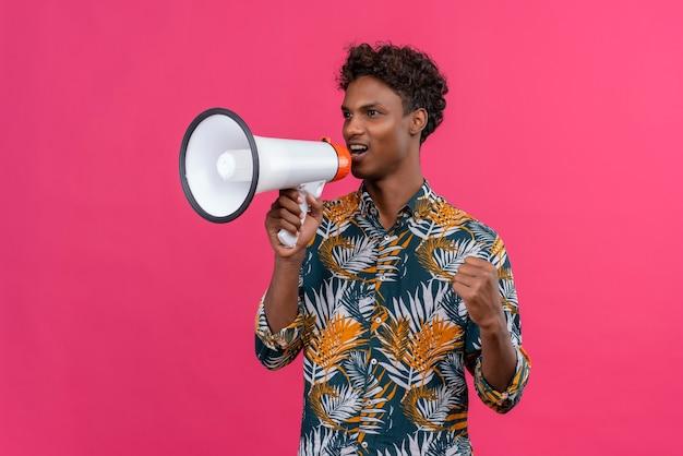 Poważny i pewny siebie przystojny ciemnoskóry mężczyzna z kręconymi włosami w koszulce z nadrukiem w liście mówiący przez megafon na różowym tle