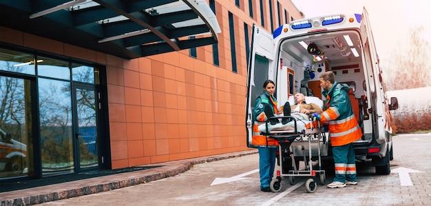 Poważny i profesjonalny zespół lekarzy w karetce wjeżdżającej na pacjenta do szpitala w sytuacji awaryjnej.