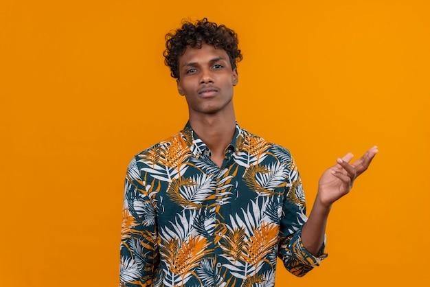 Poważny i rozważny młody przystojny ciemnoskóry mężczyzna z kręconymi włosami w koszulce z nadrukiem liści patrząc na kamery, podnosząc rękę na pomarańczowym tle
