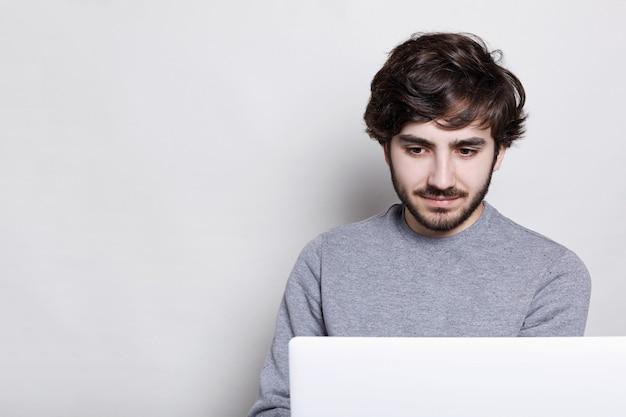 Poważny i skoncentrowany młody brodaty facet ubrany w swobodny szary sweter za pomocą laptopa