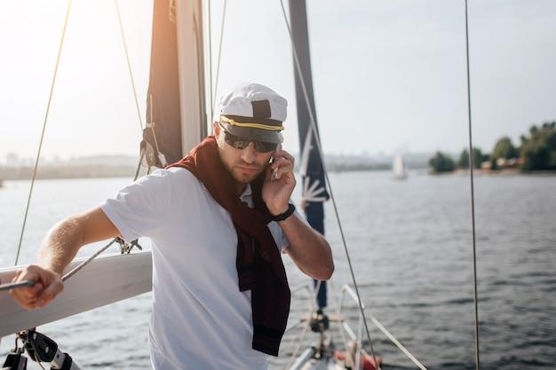 Poważny i skoncentrowany żeglarz stoi i opiera się o poręcz. trzyma telefon w dłoni i patrzy w dół. facet pracuje. na zewnątrz jest zachód słońca.