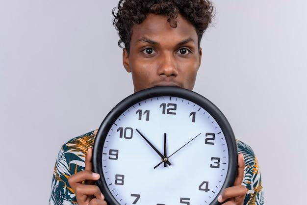 Poważny i surowy młody przystojny ciemnoskóry mężczyzna z kręconymi włosami w koszulce z nadrukiem liści przedstawiającym zegar ścienny na białym tle
