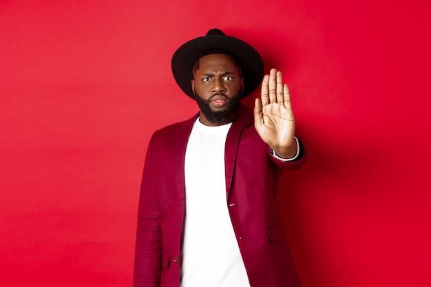 Poważny i zatroskany czarny mężczyzna wyciąga rękę, żeby cię zatrzymać
