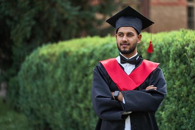 Poważny indyjski absolwent w szacie ukończenia szkoły ze skrzyżowanymi ramionami z niecierpliwością