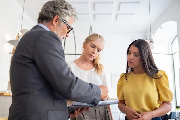 Poważny inspektor płci męskiej ze spotkaniem w notatniku i omówieniem dokumentów z młodymi przedsiębiorcami
