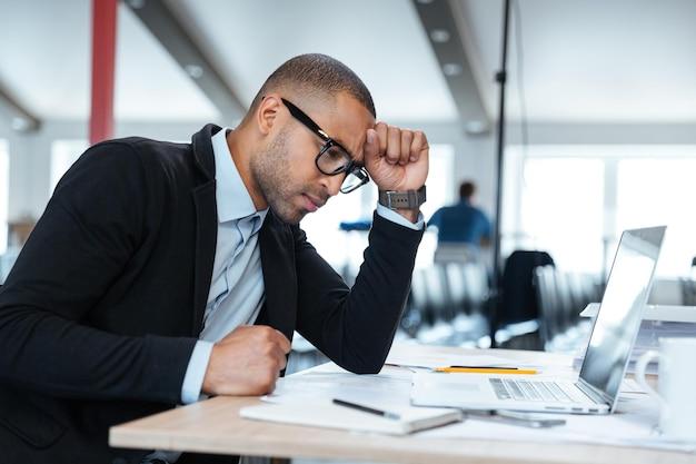 Poważny inteligentny biznesmen myślący o czymś przy użyciu laptopa w biurze
