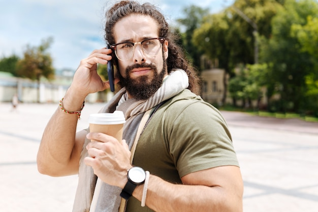 Poważny inteligentny człowiek dzwoniący, trzymając kubek z kawą