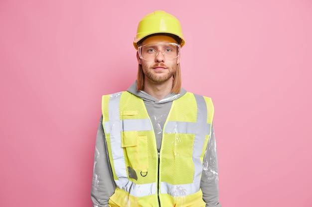 Poważny inżynier budowniczy mężczyzna nosi jednolite okulary ochronne w kasku budowlanym, który wygląda pewnie gotowy do pracy na białym tle nad różową ścianą. pewny robotnik lub pracownik budowlany
