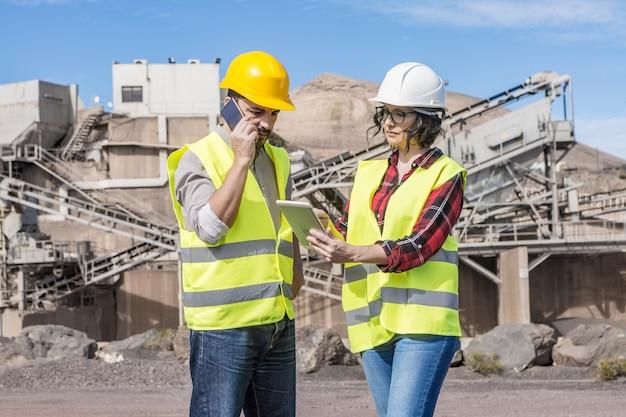 Poważny inżynier mężczyzna o rozmowie telefonicznej na smartfonie, podczas gdy koleżanka pokazuje dane na tablecie podczas spotkania na budowie obiektu przemysłowego