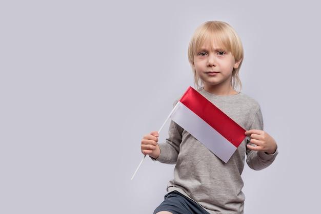 Poważny jasnowłosy chłopak trzymający flagę polski