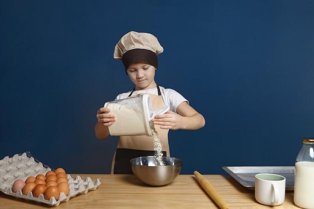 Poważny kaukaski dziecko płci męskiej o skoncentrowanym spojrzeniu podczas wlewania mąki do metalowej miski
