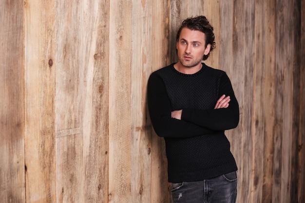 Poważny kędzierzawy młody mężczyzna w czarnym swetrze stojący ze skrzyżowanymi rękami