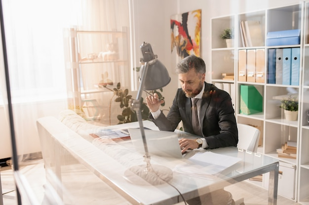 Poważny kierownik biura sprawdza pliki online