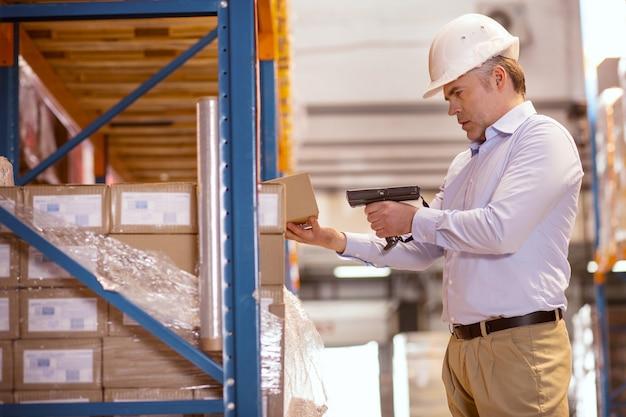 Poważny kierownik dostawy trzymający skaner podczas sprawdzania pudełek