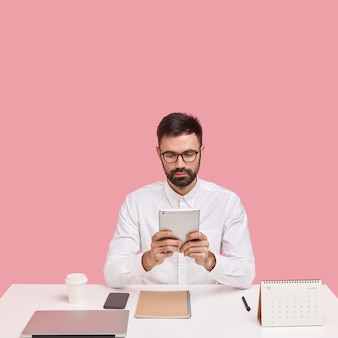 Poważny kierownik finansowy przygotowuje raport księgowy, posiada nowoczesny touchpad, monitoruje wiadomości online, bankowość, nosi okulary i formalną koszulę