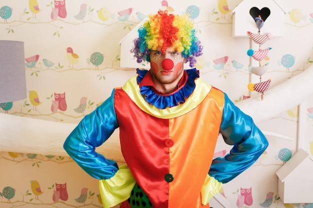 Poważny klaun w zabawnym kostiumie.