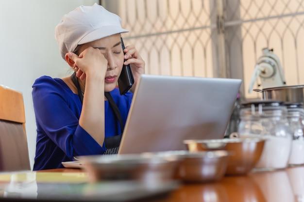 Poważny kobieta piekarz opowiada na telefonie komórkowym z laptopem i piekarnia składnikiem na stole.