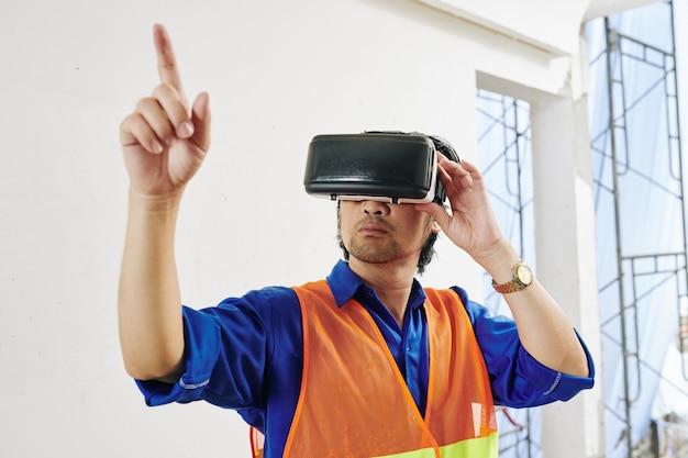 Poważny konstruktor w jaskrawej pomarańczowej kamizelce i zestawie słuchawkowym testujący aplikację rozszerzonej rzeczywistości