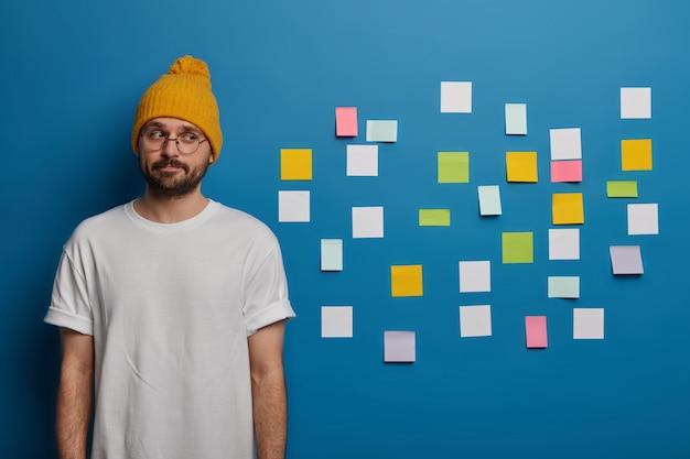 Poważny, kontemplacyjny mężczyzna z brodą, ubrany niedbale, myśli o napisaniu dyplomu, zapisuje informacje do zapamiętania za pomocą samoprzylepnych notatek.