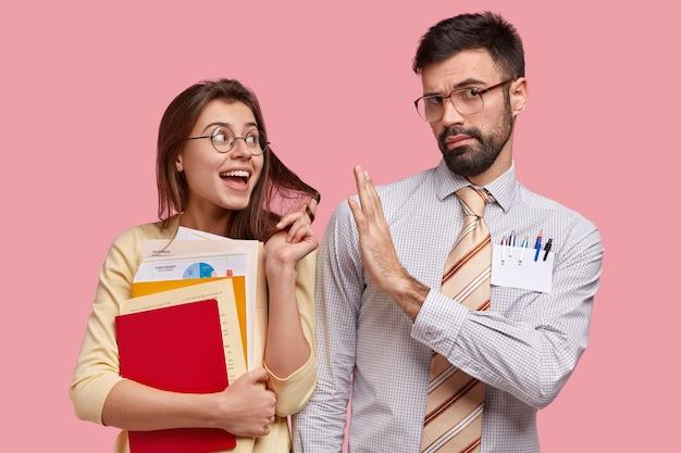 Poważny korepetytor ma lekcję ze stażystą, który flirtuje i wyraża współczucie, pokazuje gest zatrzymania, odmawia nawiązania relacji. pozytywna młoda kobieta trzyma papiery, czuje miłość do młodego nauczyciela