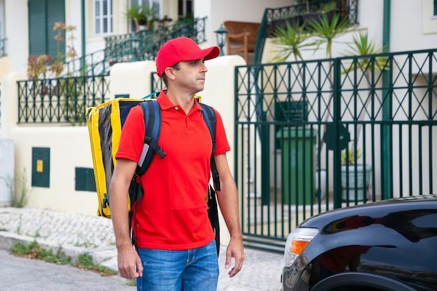 Poważny kurier z żółtym termicznym plecakiem dostarczającym ekspresowe zamówienie pieszo. skoncentrowany doręczyciel w czerwonej czapce i koszuli spacerujący po ulicy w pobliżu domu. dostawa i koncepcja zakupów online