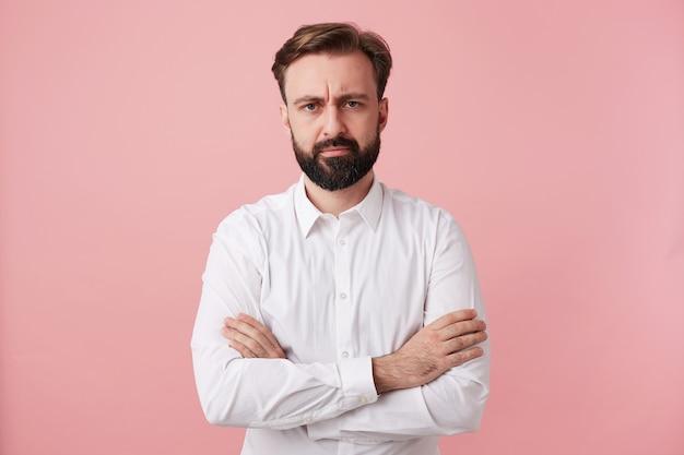 Poważny, ładny brodaty brunet z założonymi rękami marszczy brwi, patrząc do przodu, ubrany w modną fryzurę, pozując na różowej ścianie