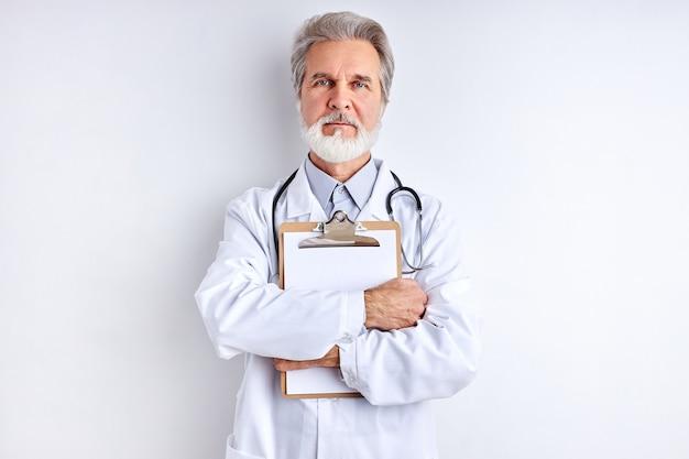 Poważny lekarz kaukaski mężczyzna pozowanie na kamery trzymając tablet w ręce
