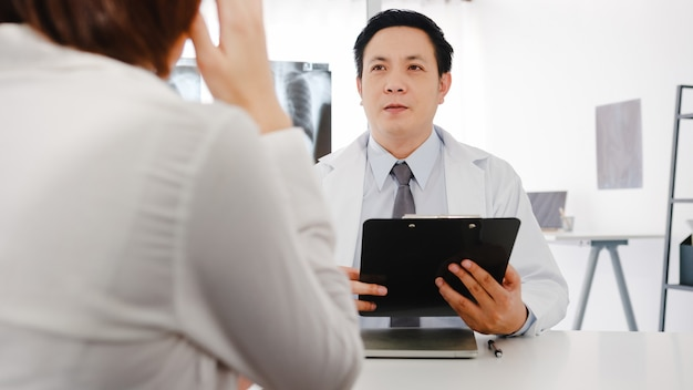 Poważny lekarz mężczyzna z azji w białym mundurze medycznym, korzystający ze schowka, dostarcza świetne wiadomości, rozmawiaj o wynikach