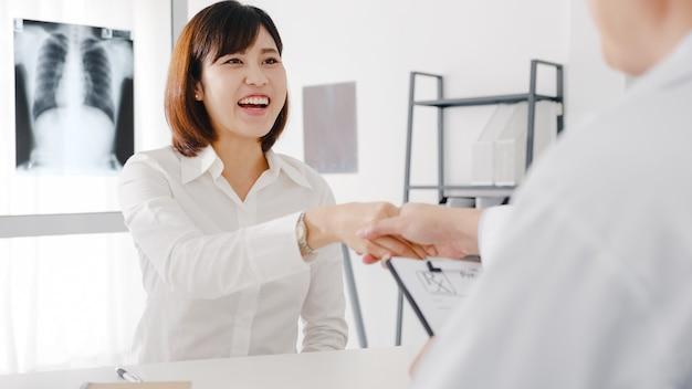 Poważny lekarz mężczyzna z azji w białym mundurze medycznym zapewnia świetne wiadomości, rozmawiaj o wynikach