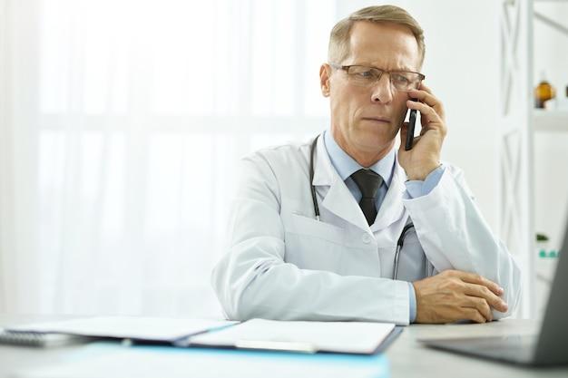 Poważny lekarz rozmawia przez telefon komórkowy i korzysta z laptopa w pracy