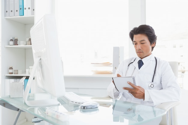Poważny lekarz spisywać notatki