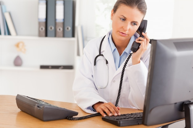 Poważny lekarz w telefonie